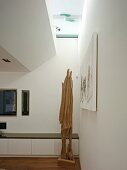 Corner of modern living room with wooden sculpture in front of low, white sideboard and narrow skylight strip