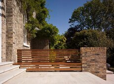 Stone terrace with bench integrated in fence adjoining old house with brick facade