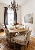 Beige gepolsterte Stühle an rustikalem Esstisch mit Kronleuchter in Wohnzimmerecke mit traditionellem Flair