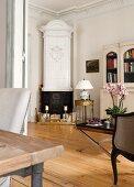 Antiker weißer Kaminofen und edles rundes Beistelltischchen in Wohnzimmerecke mit traditionellem Flair
