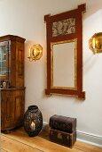 Nostalgischer Truhenstapel und Windlicht auf Holzboden vor Wandspiegel mit vergoldetem und bemaltem Rahmen, seitlich Wandleuchter aus Messing