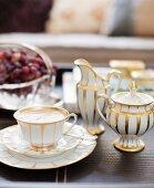 Traditionelles weißes Kaffeegeschirr mit Goldmuster, Zuckerdose und Milchkännchen
