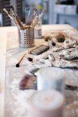 Verschiedene Pinsel in Metallbehälter auf Künstler-Arbeitstisch