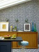Black counter, fifties-style pale-wood sideboard and wallpaper with retro pattern