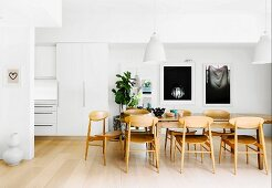Large wooden table, Scandinavian wooden chairs and white walls in open-plan dining area