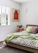 Modern artwork next to bed with graphic-patterned bedspread and scatter cushions