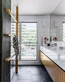 Fitted washstand and wooden towel rack in modern designer bathroom with charcoal-grey tiles