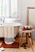 Large seashell on rustic wooden stool next to free-standing bathtub below window in bathroom with maritime atmosphere