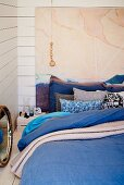 Futon bed with blue bed linen and stacked scatter cushions on floor against painting on white wooden wall