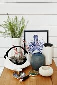 Succulents planted in white, basket-shaped china dish, various vases and picture of octopus against white wooden wall