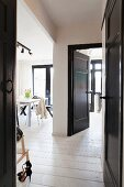 Open, black-painted interior door with view of dining area in black and white interior
