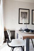 White-painted, retro-style wooden chair at modern dining table with solid-wood top