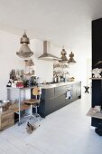 Shelves on castors and retro bar stool next to modern kitchen counter below industrial-style pendant lamps in rustic interior