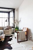 Leather armchair with wooden frame on white wooden floor, and retro standard lamp in front of window
