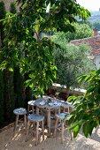 Rustikaler Sitzplatz, Holzhocker um runden Tisch auf Terrasse, unter Zitronenbaum