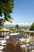 Metallstühle um Tisch auf Terrassenplatz, Blick über Steinbalustrade auf mediterrane Landschaft