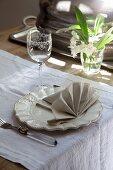 Gedeck mit dekorativ gefalteter Stoffserviette auf weißem Tischläufer, seitlich Blumen im Glas