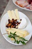 Käseplatte mit Nussmischung, dekoriert mit Olivenzweig