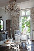 Runde Tische und weiss lackierte Stühle, im Hintergrund französische Tür