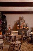 Holzklappstühle um Bistrotisch, im Hintergrund antiker Konsolentisch mit Steinbüste in kellerartigem Raum mit Weinlager