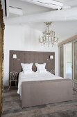 Elegantes Doppelbett mit gepolstertem Kopfteil, darüber Kronleuchter mit Glasschmuck