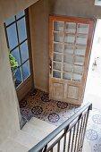 Blick von Treppe in Diele mit gemusterten Fliesenboden, offene Haustür aus abgelaugtem, hellem Holz