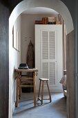 Blick durch Rundbogen auf rustikalen Tisch und Hocker aus Holz, im Hintergrund weisser Schrank mit Lamellentür