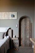 Rundbogen mit rustikaler Holztür in grau getönter Wand in elegantem Schlafzimmer