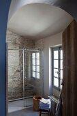 Blick auf verglaste Dusche mit Natursteinfliesen an Wand