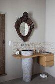 Waschtisch mit konischem Standwaschbecken in Holzplatte und Schubladenelement, oberhalb antiker Spiegel an Wand, in Badezimmerecke