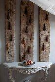 Geschwungener Konsolentisch im Rokoko Stil, oberhalb Vintage Holzbohlen an Wand