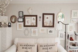 White sofa with hessian scatter cushions below pictures and picture frames on wall