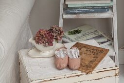 Dried hydrangeas in white china pot and pink ballet shoes on lace doily