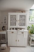 White dresser with lace curtains behind glass door panels
