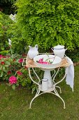 Wash basin and pitcher on vintage metal stand in garden