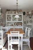 Rustic dining table and white wooden chairs in front of dresser in cosy kitchen-dining room