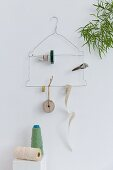 Wire coat hanger used as organiser for reels of twine, labels and ribbons