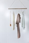 Clothes rail made from broom handle and wire coat hangers