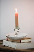 Lit candle on candlestick made from bent vintage fork and saucer on stack of books