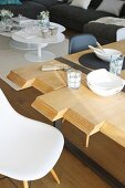 Tischplatte aus Holzbohlen unterschiedlicher Längen, Coffeetable im Hintergrund
