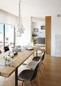 Leuchtenbündel über schlichtem Designerholztisch mit Eames Plastic Chairs; im Hintergrund eine Schiebetür zur Küche