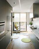 Zweizeilige, moderne Küche mit Stangengriffen an grauen Fronten; im Hintergrund ein Kinderhochstuhl vor der Schiebetür zur Dachterrasse