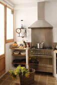 Modern, stainless steel cooker and extractor hood next to shelves of crockery with shopping basket in foreground