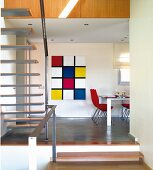 View from staircase of dining area with Piet Mondrian-style artwork on wall in modern, open-plan interior