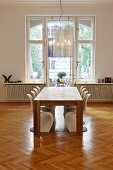 Wooden table and white plastic shell chair in front of window in period apartment with minimalist ambiance