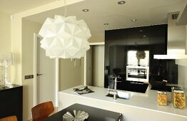 Designer pendant lamp above dining area in front of open-plan kitchen; black, glossy fitted cabinets with appliances in background