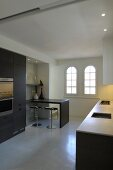Minimalist kitchen counter opposite fitted cabinets with kitchen appliances and breakfast bar with bar stools; arched windows in background