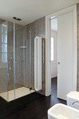 Modernes Bad mit weissen Sanitärobjekten, gegenüber Glas Duschkabine vor gefliesten Wänden