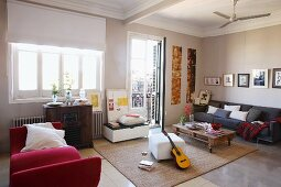 Modern furnishings, red couch, white stool and low table on castors in front of sofa in spacious living room with traditional ambiance