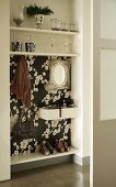 Wardrobe integrated into niche with floral black and white wallpaper and glass ornaments on shelves